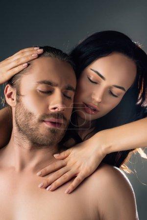 Photo pour Jeune amie passionnée caressant un copain isolé sur le gris avec la lumière du dos - image libre de droit