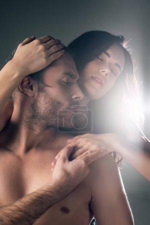 Photo pour Un jeune couple passionné blotti sur le gris avec la lumière du dos - image libre de droit
