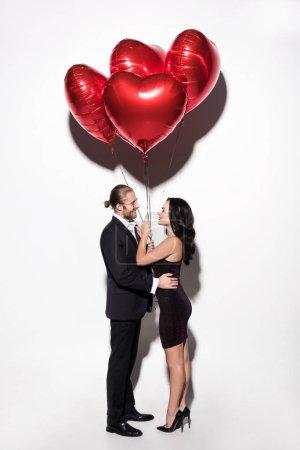 Photo pour Beau couple heureux tenant des ballons en forme de coeur rouge sur valentins jour sur blanc - image libre de droit