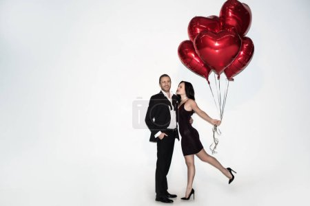 Photo pour Beau couple positif tenant des ballons en forme de coeur rouge sur valentins jour sur blanc - image libre de droit