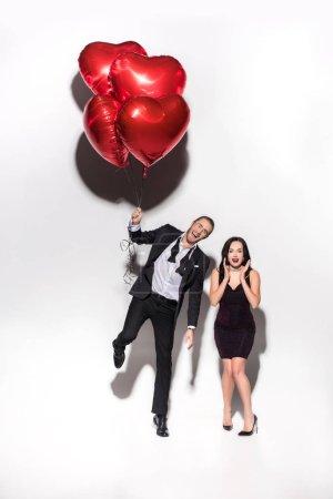 Photo pour Couple excité tenant des ballons en forme de coeur rouge sur valentins jour sur blanc - image libre de droit
