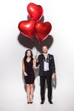 Photo for Beautiful smiling couple holding red heart shaped balloons on valentines day on white - Royalty Free Image