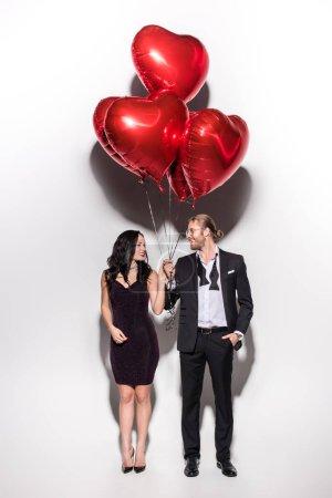 Photo pour Un couple souriant tenant des ballons en forme de coeur rouge sur des valentins - image libre de droit