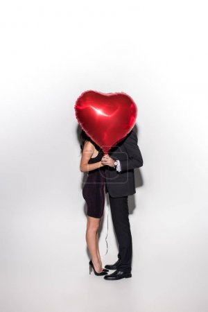 Photo for Couple holding red heart shaped balloon in front of face on valentines day on white - Royalty Free Image