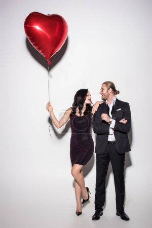 Photo for Happy couple holding red heart shaped balloon on valentines day on white - Royalty Free Image