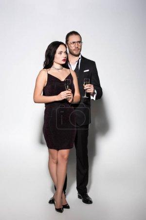 Photo pour Beau couple en costume et robe tenant des verres à champagne pour la Saint Valentin sur blanc - image libre de droit