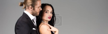 Photo for Panoramic shot of beautiful young couple in black suit and dress isolated on grey - Royalty Free Image