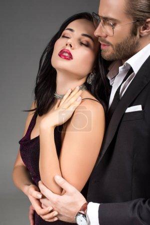Photo pour Couple tendre en costume noir et robe câlin isolé sur gris - image libre de droit