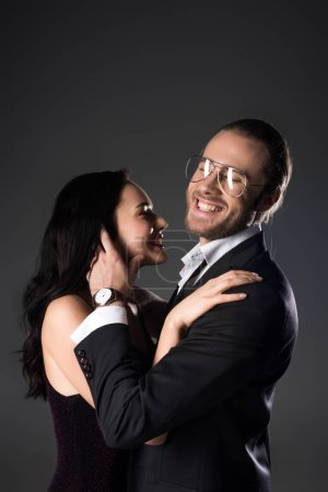 Photo for Beautiful cheerful couple in black suit and dress isolated on grey - Royalty Free Image