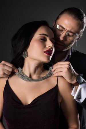 Photo pour Homme portant un collier sur sa jolie petite amie en valentins jour, isolé sur gris - image libre de droit