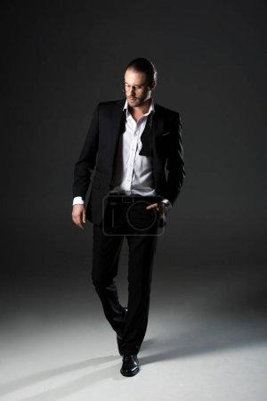 Photo pour Bel homme en élégant costume noir sur gris - image libre de droit