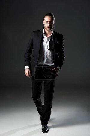 Photo pour Confiant bel homme posant en costume sur gris - image libre de droit