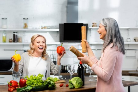 Photo for Smiling woman holding bell peppers and her asian friend holding Pepper Mill and salt mill - Royalty Free Image