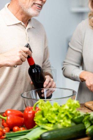 Photo pour Vue dégagée d'une femme cuisinière et d'un homme ouvrant une bouteille de vin - image libre de droit
