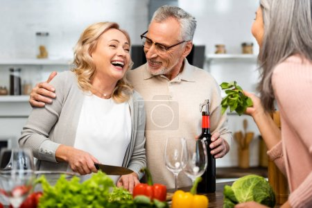 Photo for Smiling woman cooking and talking with her friends in kitchen - Royalty Free Image