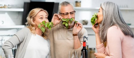 Photo for Panoramic shot of smiling friends smelling basil in kitchen - Royalty Free Image