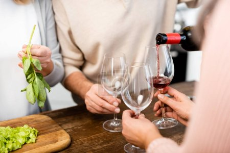 Photo for Cropped view of man pouring wine to glasses for friends - Royalty Free Image