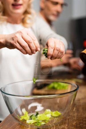 Photo for Cropped view of woman adding lettuce to bowl in kitchen - Royalty Free Image