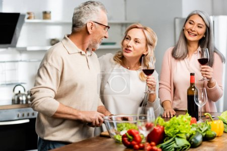 Photo for Smiling multicultural woman holding wine glasses and man cutting lettuce in kitchen - Royalty Free Image