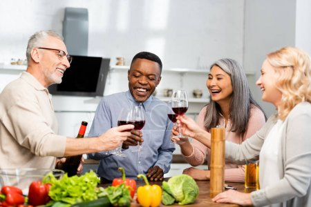 Photo for Smiling multicultural friends clinking with wine glasses in kitchen - Royalty Free Image