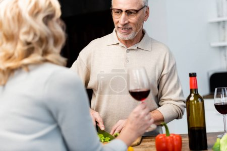 cropped view of woman talking with smiling friend and he cutting lettuce