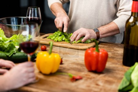 Photo for Cropped view of woman holding wine glass and man cutting lettuce - Royalty Free Image