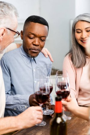 Photo for Cropped view of smiling multicultural friends clinking with wine glasses in kitchen - Royalty Free Image