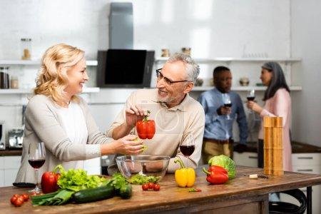 Photo pour Foyer sélectif de la femme ajoutant laitue et homme souriant tenant poivron, amis multiculturels parlant sur fond - image libre de droit