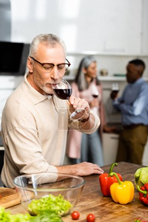 Photo for Selective focus of man drinking wine and multicultural friends talking on background - Royalty Free Image