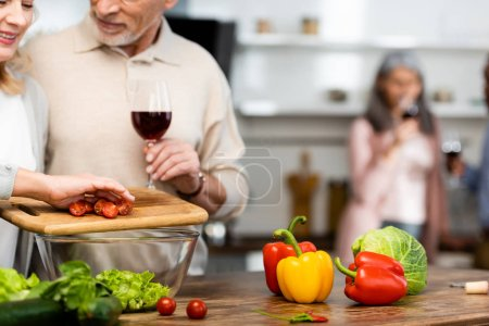 Photo for Cropped view of smiling woman adding cut cherry tomatoes to bowl and man holding wine glass - Royalty Free Image