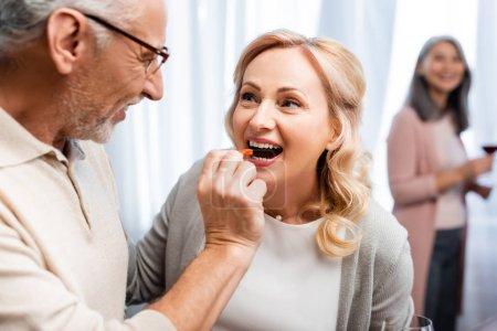 Photo pour Un homme souriant donne du poivron coupé à son ami souriant - image libre de droit