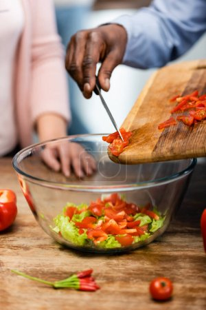 Photo for Cropped view of african american man adding cut bell pepper to bowl and woman standing near him - Royalty Free Image