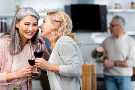 Foto de Enfoque selectivo de sonriente mujer diciendo secreto a asiático amigo con copa de vino - Imagen libre de derechos