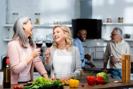 Photo pour Foyer sélectif des amis souriants multiculturels tenant des verres à vin dans la cuisine - image libre de droit