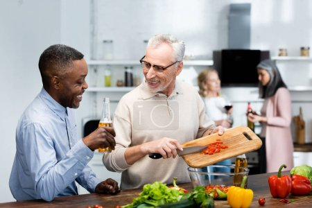 Photo for African american man holding beer and his friend adding cherry tomatoes to salad - Royalty Free Image