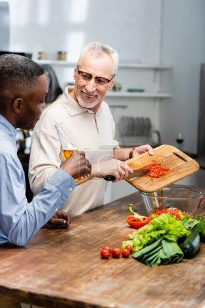 Photo pour Africain américain tenant de la bière et son ami ajoutant des tomates cerises à la salade - image libre de droit