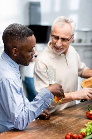 Photo for African american man holding beer and his smiling friend cooking in kitchen - Royalty Free Image