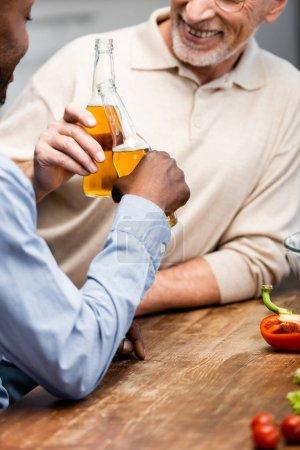 Photo pour Crochet vue d'un Africain américain serrant la main avec son ami souriant dans la cuisine - image libre de droit