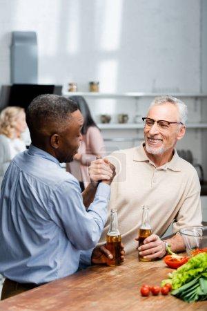 Photo pour Africain américain tenant la main et parlant avec un ami souriant dans la cuisine - image libre de droit