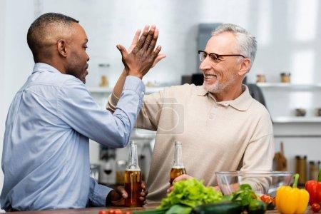 Foto de Africano americano hombre dando choca cinco a sonriente amigo con cerveza en cocina - Imagen libre de derechos