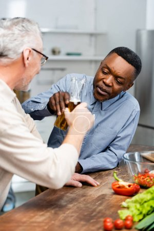 Photo pour Focus sélectif of african american man clinking with his friend in kitchen - image libre de droit