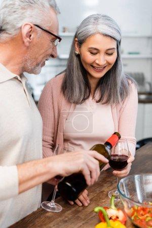 Photo pour Homme souriant versant du vin pour son ami asiatique dans la cuisine - image libre de droit