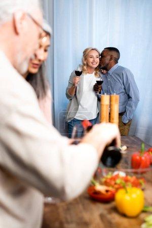 Photo pour Focus sélectif d'un Africain américain embrassant son ami souriant dans la cuisine - image libre de droit