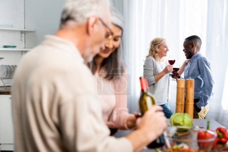 selective focus of african american man talking with smiling friend in kitchen
