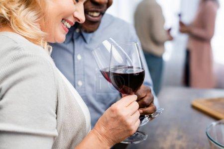 Photo pour Crochet vue d'un Africain américain claironnant avec un ami souriant dans la cuisine - image libre de droit