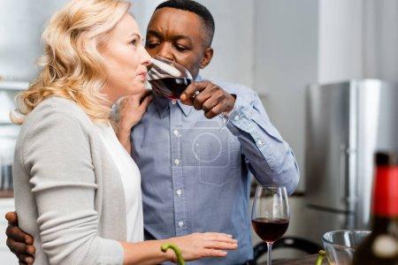 Foto de Enfoque selectivo del hombre afroamericano dando copa de vino a un amigo en la cocina - Imagen libre de derechos