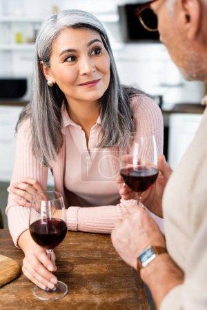 Photo pour L'accent sélectif d'une femme asiatique souriante qui parle à son ami - image libre de droit