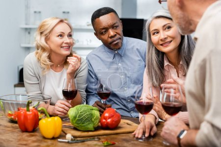 Photo for Selective focus of multicultural friends talking and holding wine glasses - Royalty Free Image