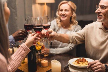 Photo pour Focalisation sélective des amis multiculturels souriants se claquant pendant le dîner - image libre de droit