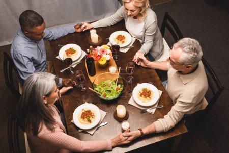 Photo pour Vue d'ensemble des amis multiculturels se tenant la main et priant pendant le dîner - image libre de droit